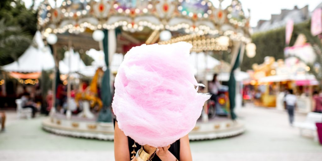 woman with gigantic cotton candy in front of merry-go-round